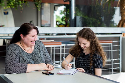 Two women sitting at a table. One woman is writing in a notebook